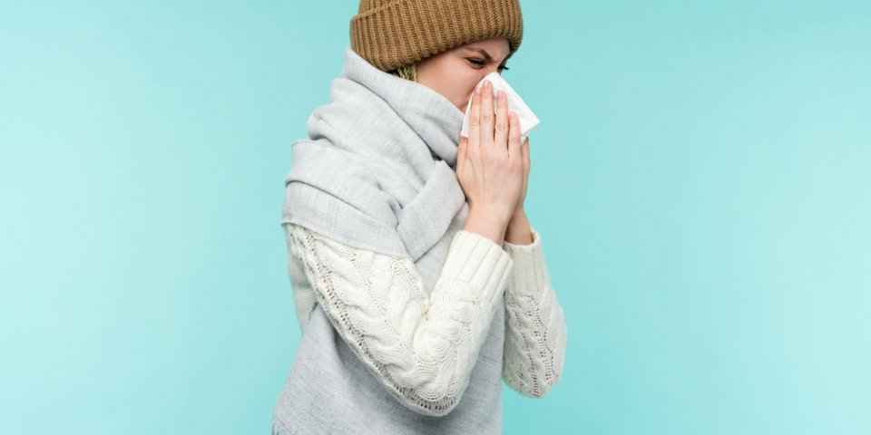 health and medicine concept - young woman blowing nose into tissue, on a blue background pretty girl cold with snot