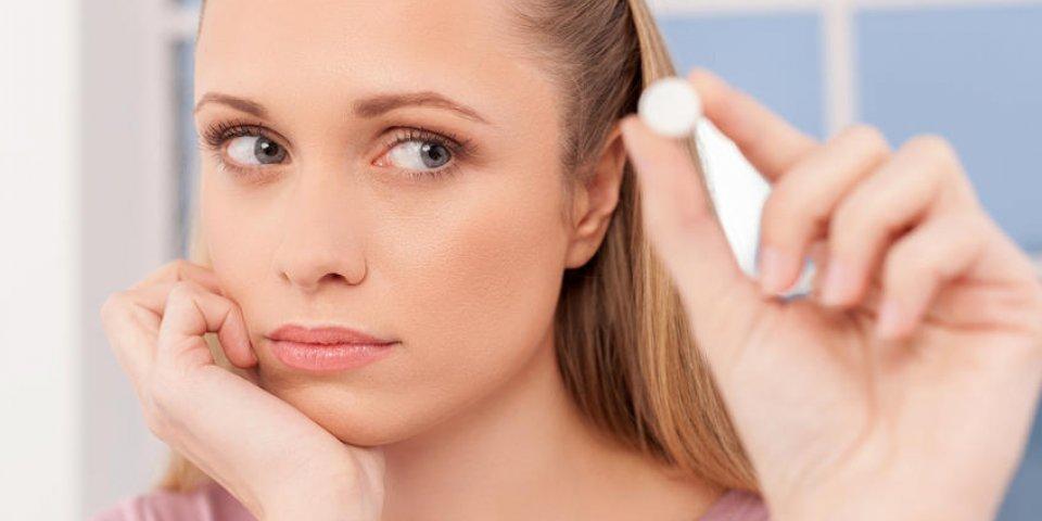 jeune femme déprimée tenant une pilule et la regardant
