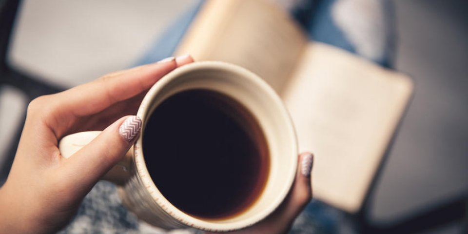 fille ayant une pause avec une tasse de café après avoir lu des livres ou étudié