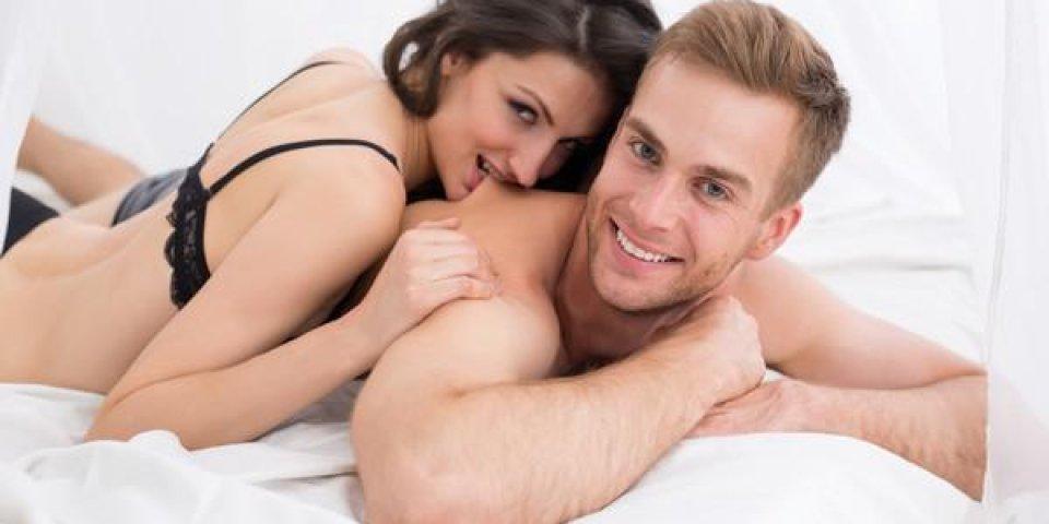 heureux jeune couple couché dans un lit blanc, en regardant la caméra fille étreindre guy et ludique mordant un mec da...
