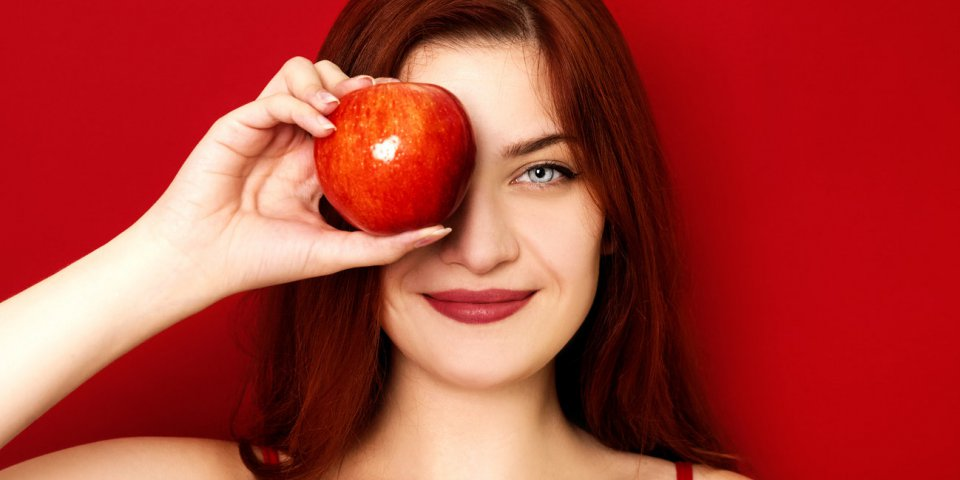 young smiling woman holding apple