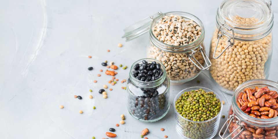 healthy food, dieting, nutrition concept, vegan protein source assortment of colorful legumes in jars, lentils, soy kidne...