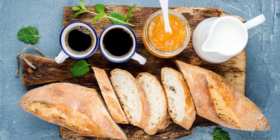 breakfast set baguette, orange jam and coffee in cups on rustic wooden board over concrete grey-blue background top view