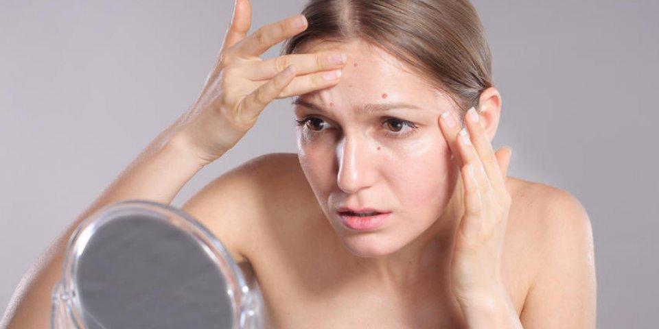 jeune femme presser son acné devant le concept de soins de la peau miroir femme
