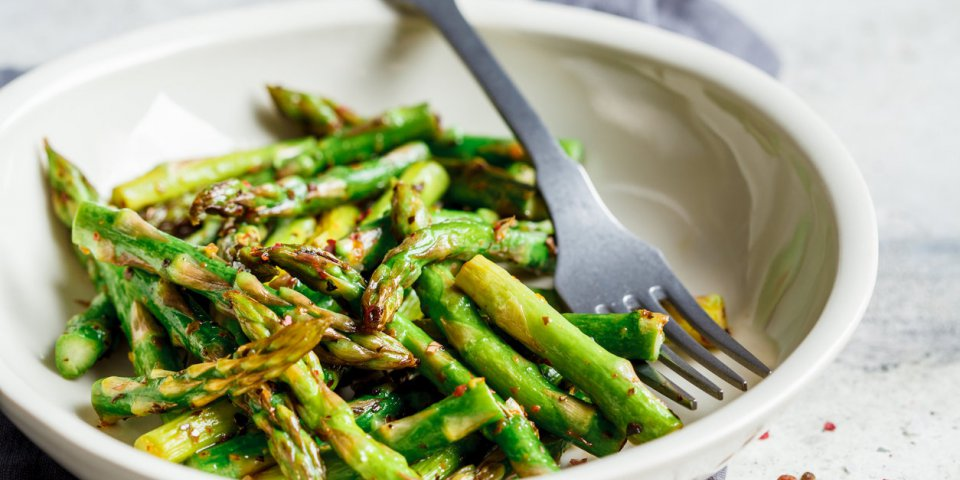 cooked green asparagus with pepper and salt in a white bowl