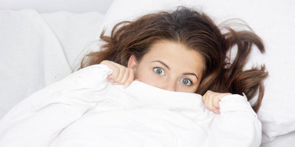 jeune femme effrayée au lit