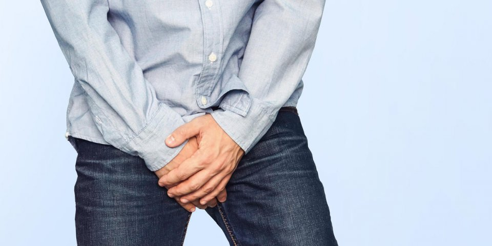 close up of a man with hands holding his crotch on a light blue background urinary incontinence men's health the pain fro...