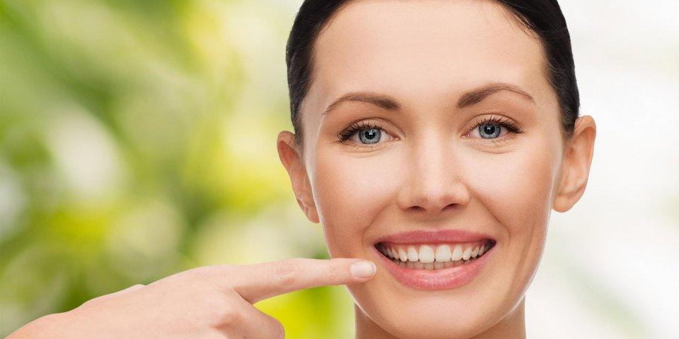 concept de santé, spa et beauté - visage propre de la belle jeune femme pointant vers sa bouche