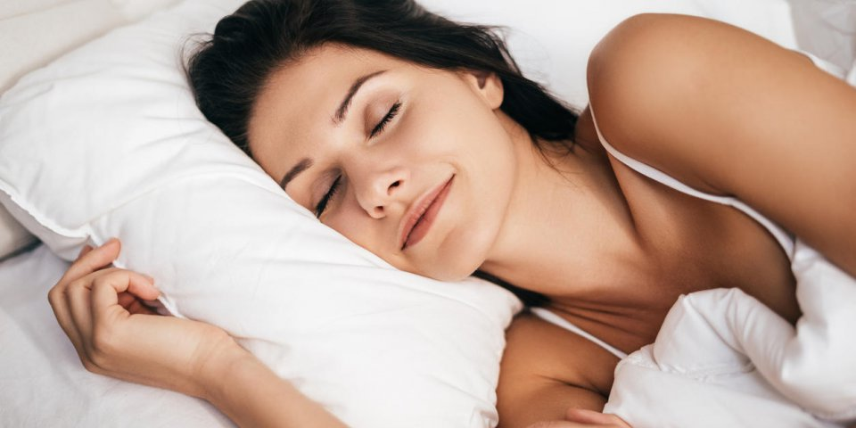 belle jeune femme souriante pendant le sommeil tout en se trouvant dans le lit à la maison