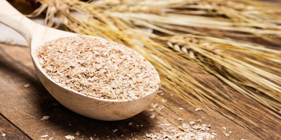 gros plan de cuillère en bois rempli de son de blé sur le fond des épis de blé supplément alimentaire pour améliore...