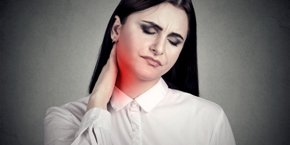 woman massaging painful neck colored in red isolated on gray wall background human face expression