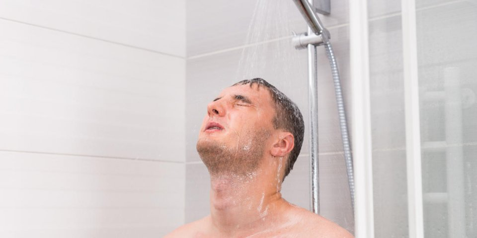 young man with closed eyes taking a shower, standing under flowing water in shower cabin with transparent glass doors in ...