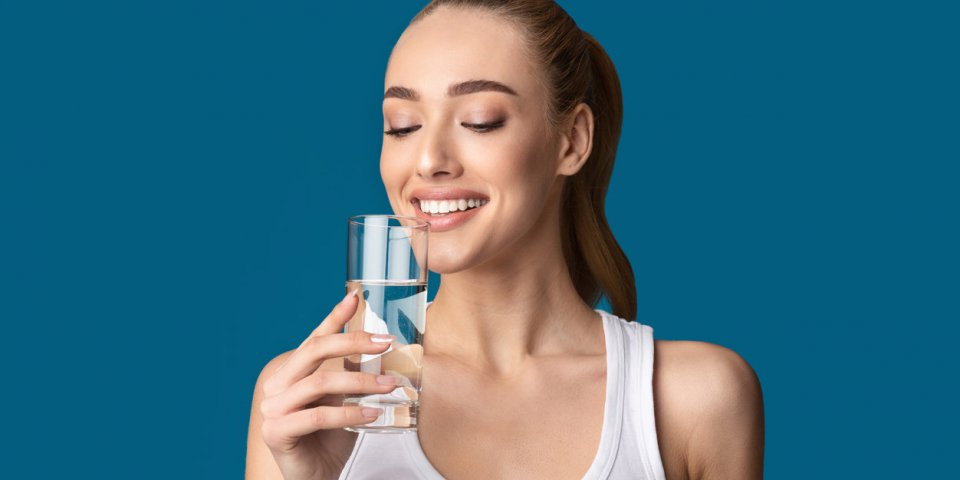 happy girl drinking glass of water standing on blue studio background healthy lifestyle concept