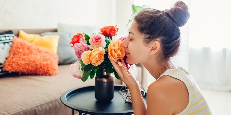 woman smelling fresh roses in vase on table housewife taking care of coziness in apartment interior design and decor with...