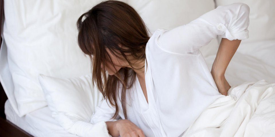 tired young woman waking up in white bedroom feeling back pain, exhausted female suffering from sudden discomfort after b...