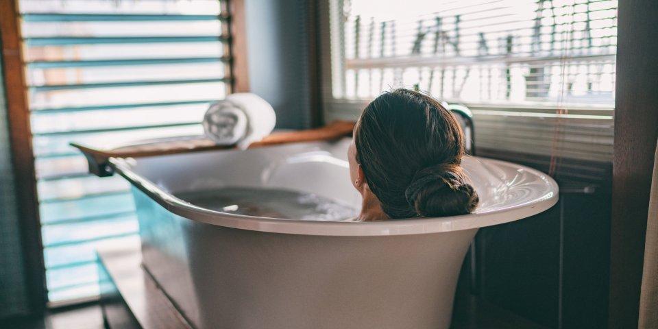 bath taking woman relaxing in bathtub of hotel room at luxury overwater bungalow resort in bora bora, tahiti