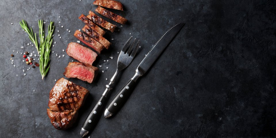 grilled sliced beef steak on stone table top view with copy space